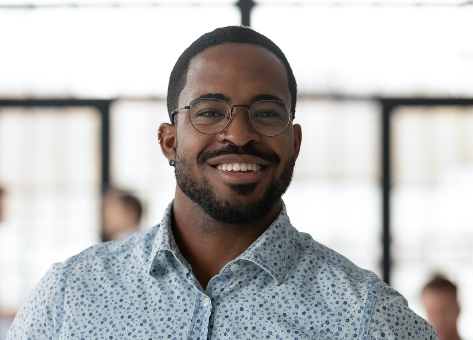 Headshot portrait of smiling African American businessman in glasses posing looking at camera in office, happy biracial male boss or CEO feel motivated show confidence and success, leadership concept